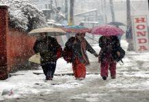 Kashmiri students walk amid snowfall