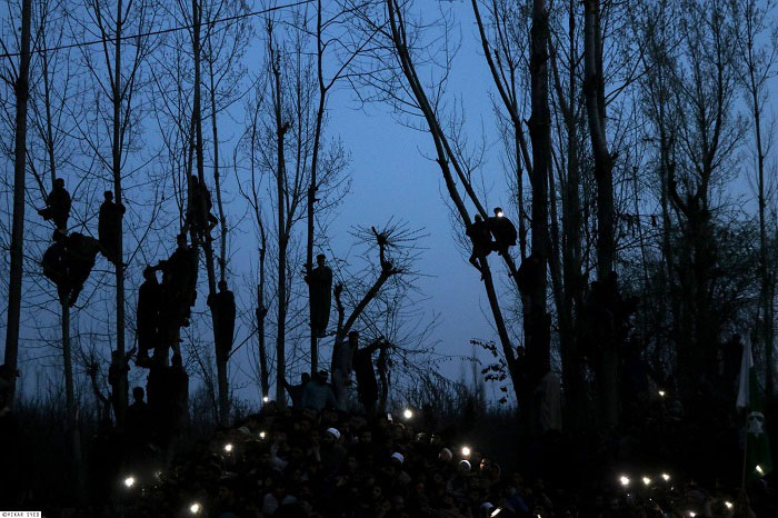 People hang on trees to get a last glimpse of Rayees Kachroo during evening time at his native village Below in Pulwama