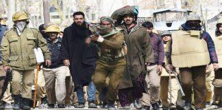 SOG personnel aims his gun at Peer Viqar Ul Aslam and his colleagues